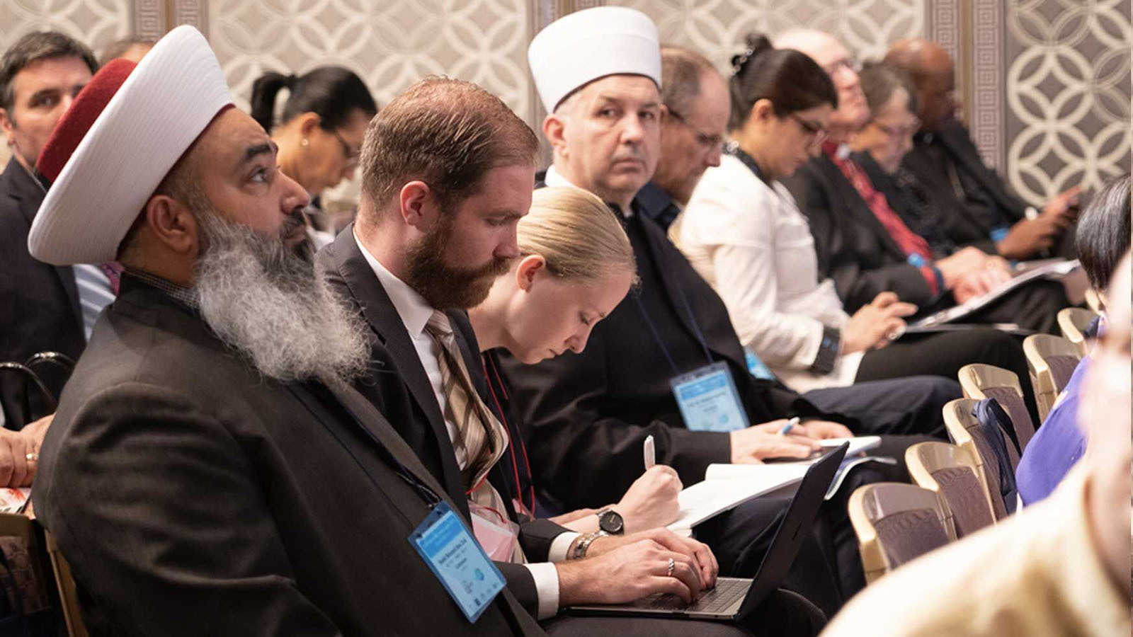 Audience members listen to the opening plenary at the 2019 Interfaith Forum.