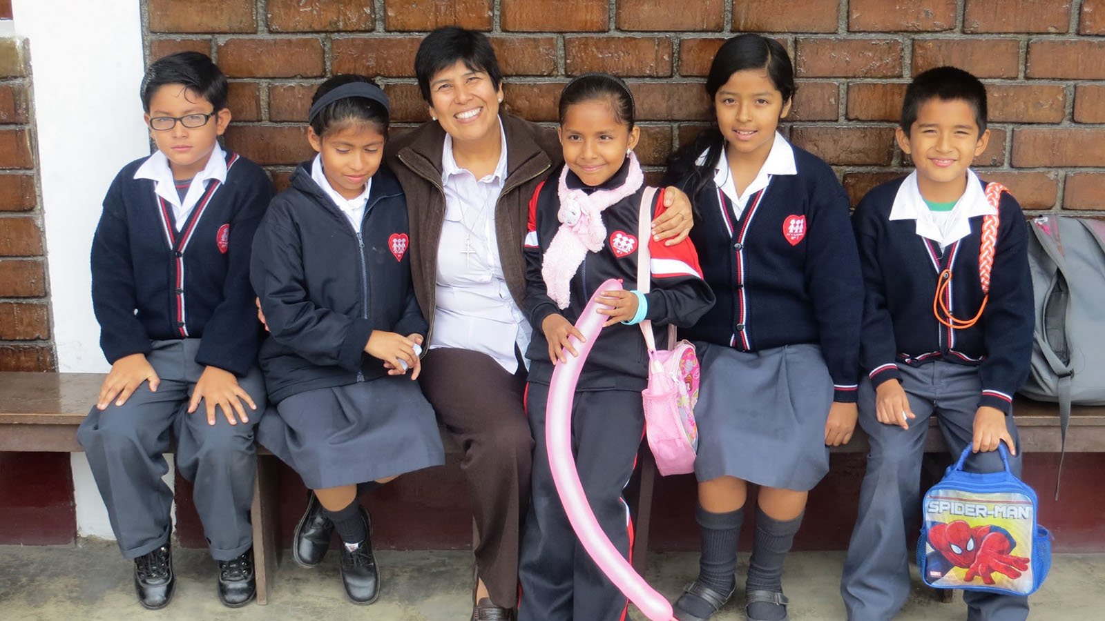 School children pose with a member of Entreculturas